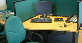 Office cubicle with chair, computer, and phone